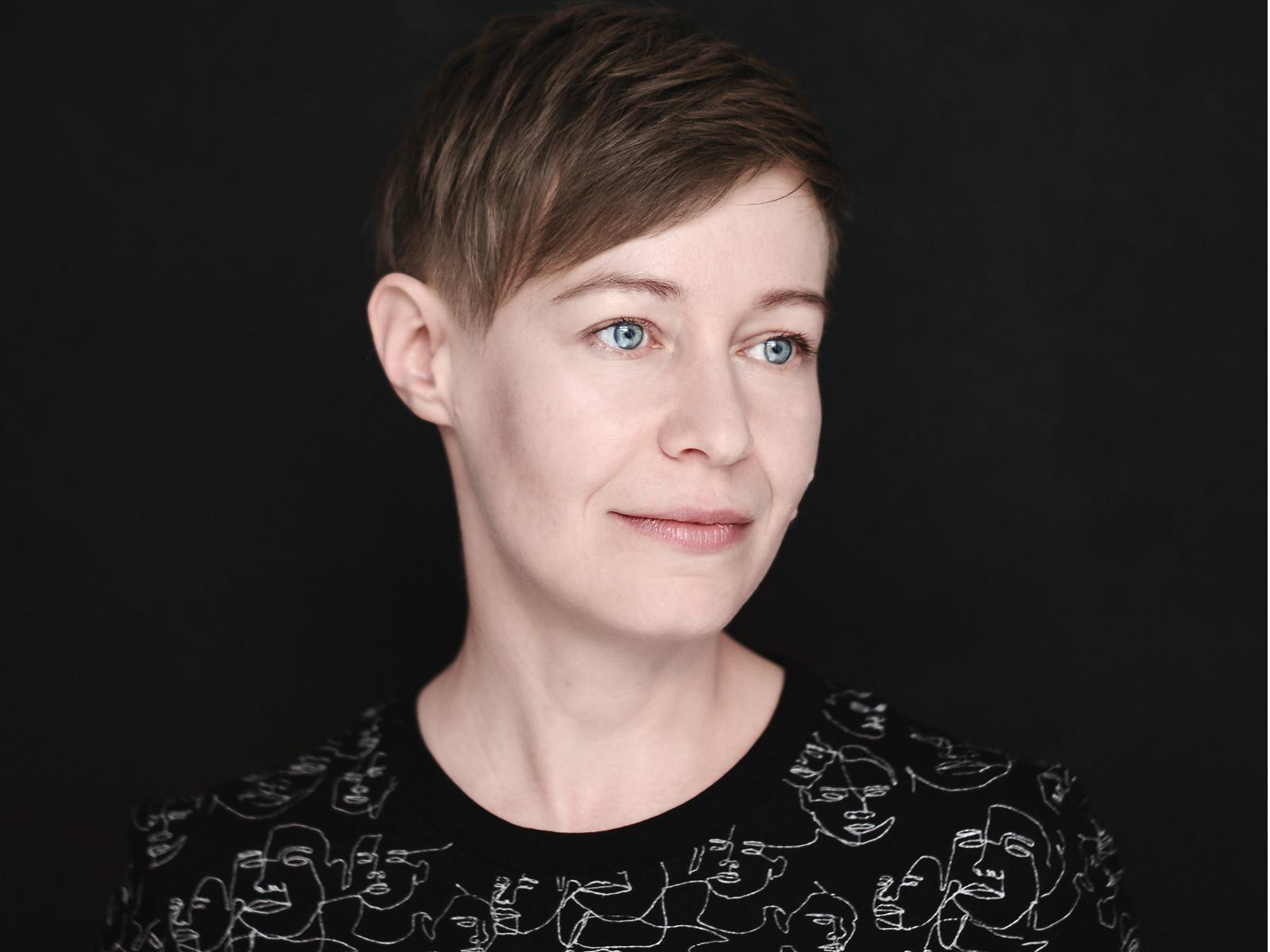 Tet ist eine Frau mit Kurzhaarschnitt, hellblauen Augen und blassen Teint. Sie ist vor einem schwarzem Hintergrund abgebildet.