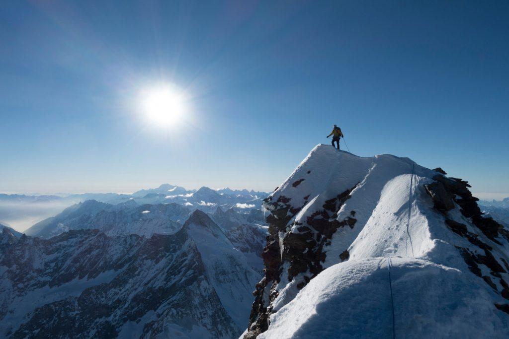 Alexander Huber auf dem schneebedeckten Matterhorn. Im Hintergrund weitere Gipfel im Sonnenschein.