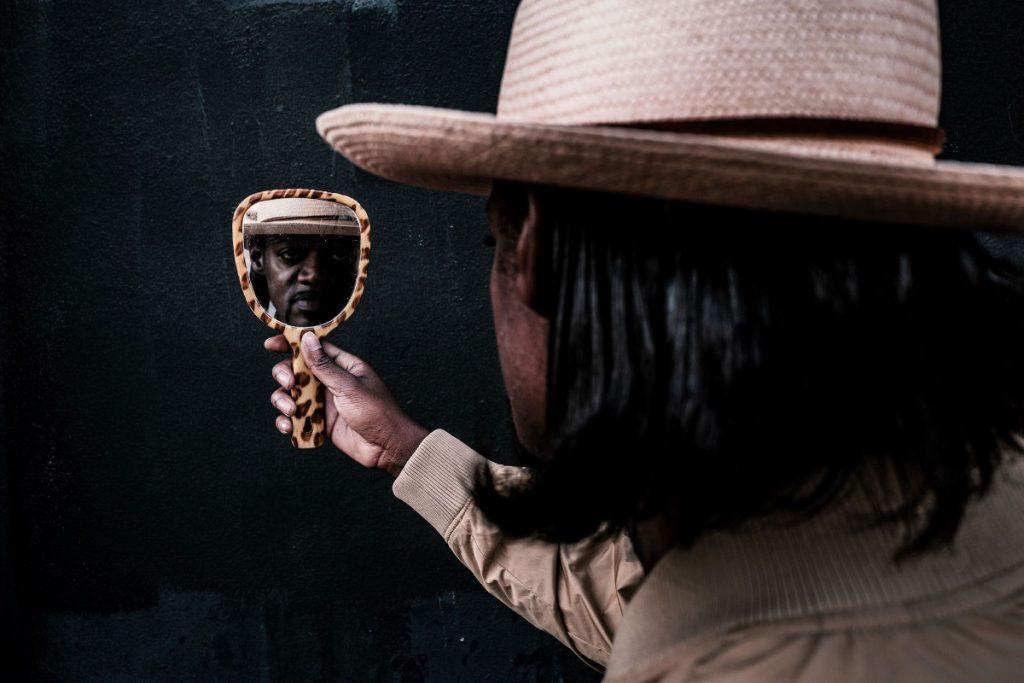 Der Musiker schaut in den Spiegel. Bei uns könnt Ihr Eric Gales Tickets gewinnen.