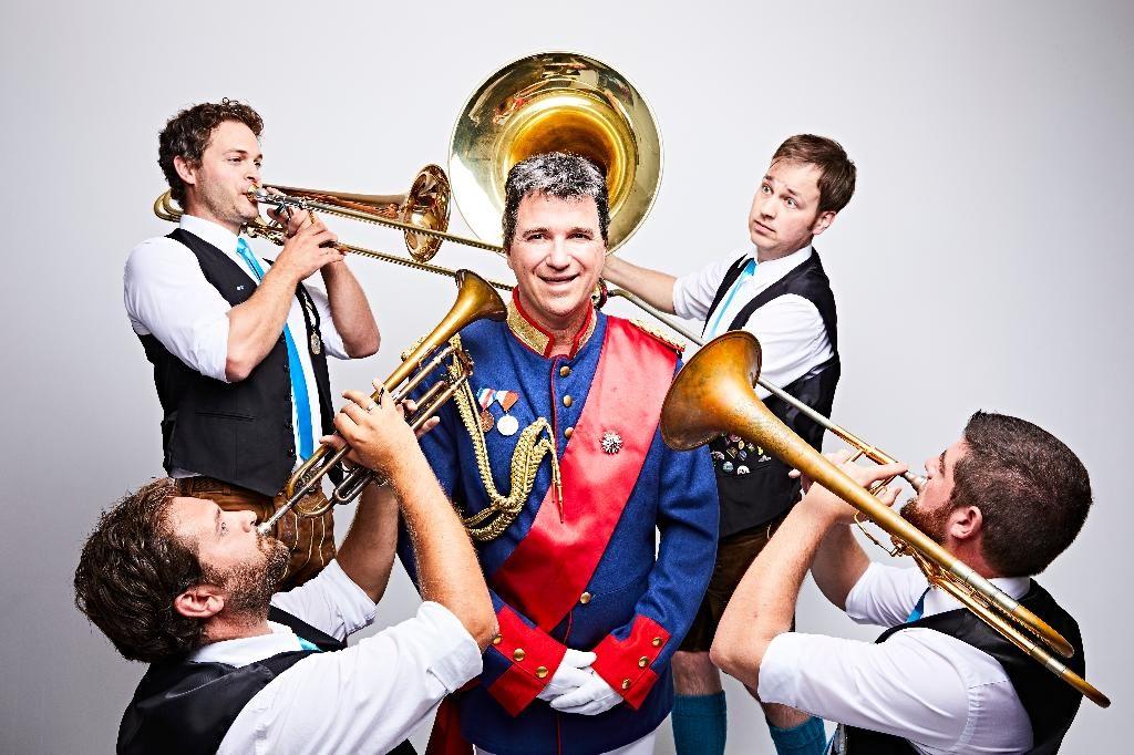 Mann in bayerischer Uniform wird von vier Musikern umringt