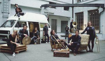 Die zehnköpfige Band Donnerbalkan um ihren Tourbus herum vor dem Münchner Studio