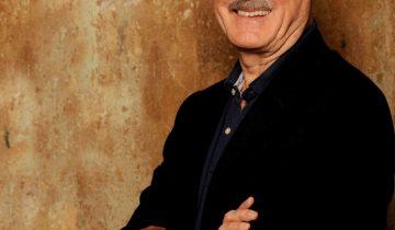 SChauspieler Joh Cleese lehnt an einer beigen Wand