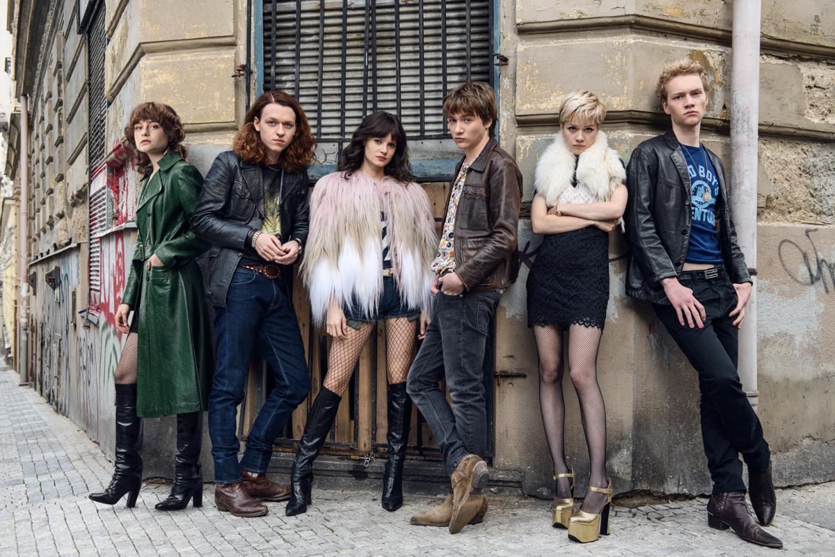 Fünf Jugendliche in extravaganter Kleidung lehnen an einer typich urbanen Berliner Mauer