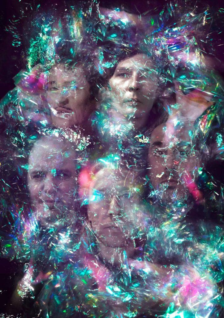 Fünf Musiker unter einer Transparenten Folie mit bunten Lichtreflexionen