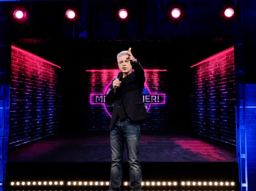 Michael Mittermeier steht gestikulierend auf einer Bühne mit LED-Hintergrund im Rahmen seiner neuen Show.