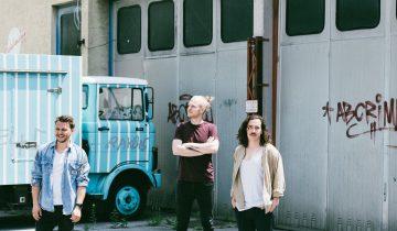 Die Austro-Pop folkshilfe stehen vor den Toren einer Lagerhalle