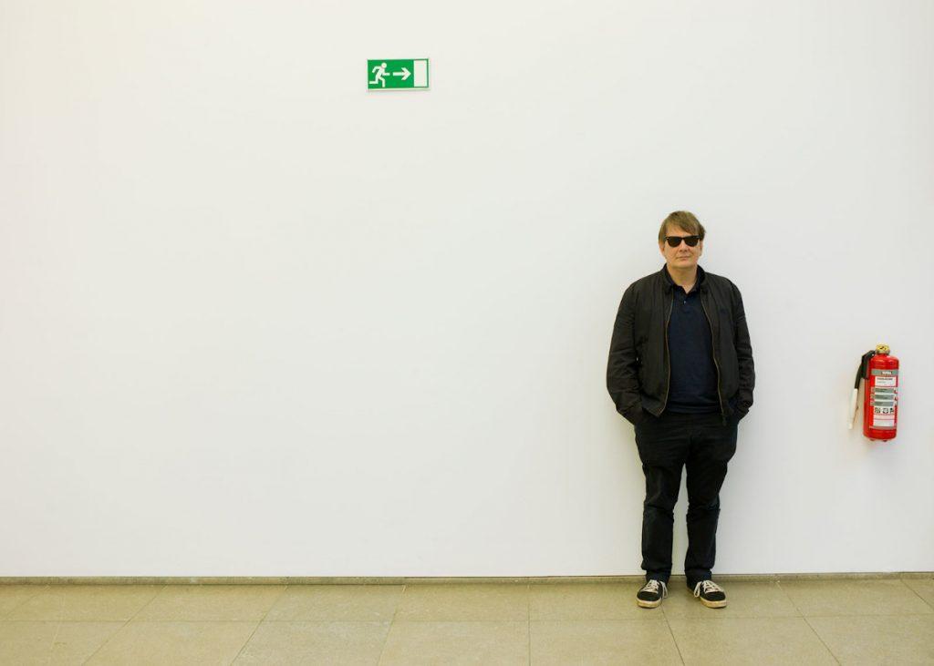 Der Autor und Musiker Sven Regener lehnt mit Sonnenbrille neben einem Feuerlöscher an der Wand.
