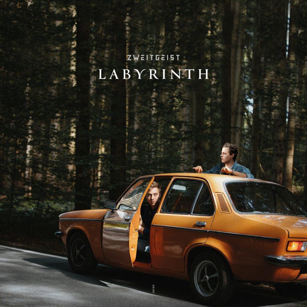 """Zweitgeist sind ein Münchner Singer-Songwriter-Duo und stehen auf dem Plattencover zu """"Labyrinth"""" mit einem oragnenen Oldtimer im Wald"""