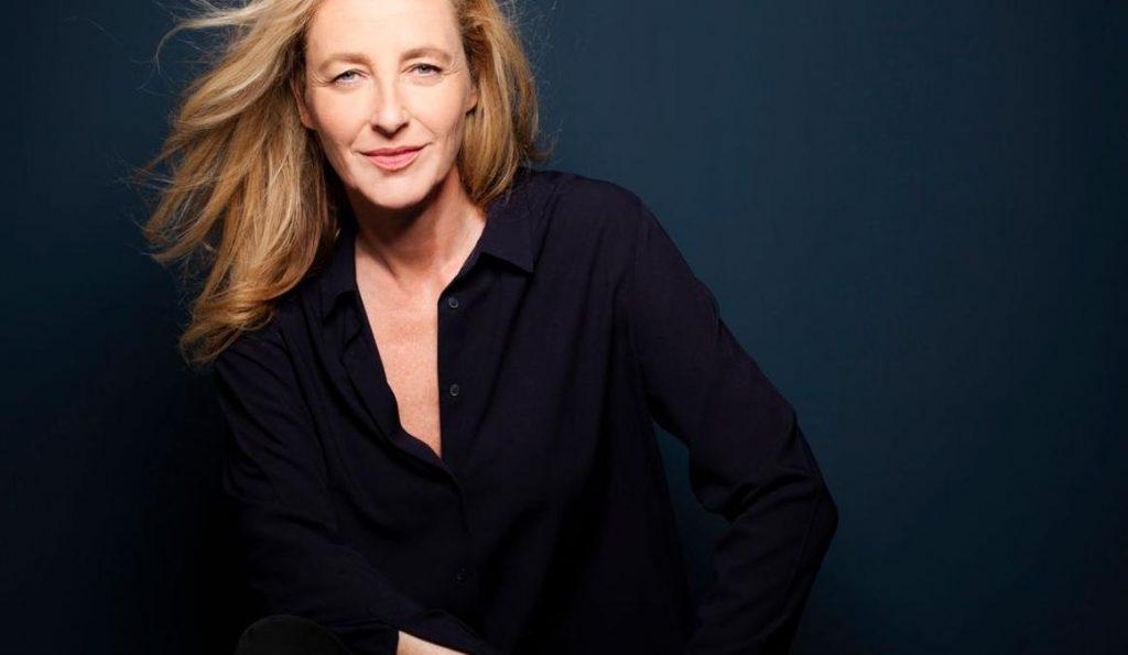 Filmfest München Pop Up: Festivaldirektorin Diana Iljine mit dunklem Anzug vor blauer Wand