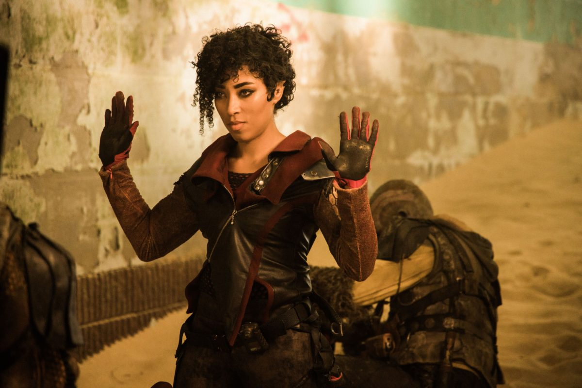 """Vargant Queen Staffel 1: Zu sehen ist eine junge Frau mit lockiger Kurzhaarfrisur. Sie trägt einen Overall und steht in einer futuristischen Straße..Sie gestikuliert """"Ich habe nichts gemacht""""."""