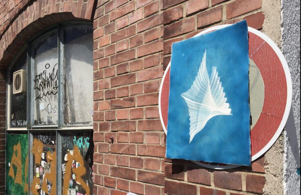 Kunst an einer Münchner Hauswand auf einem Straßenschild. Die Kunstwerke werden im öffentlichen Raum ausgestellt, und können kostenlos mitgenommen werden.