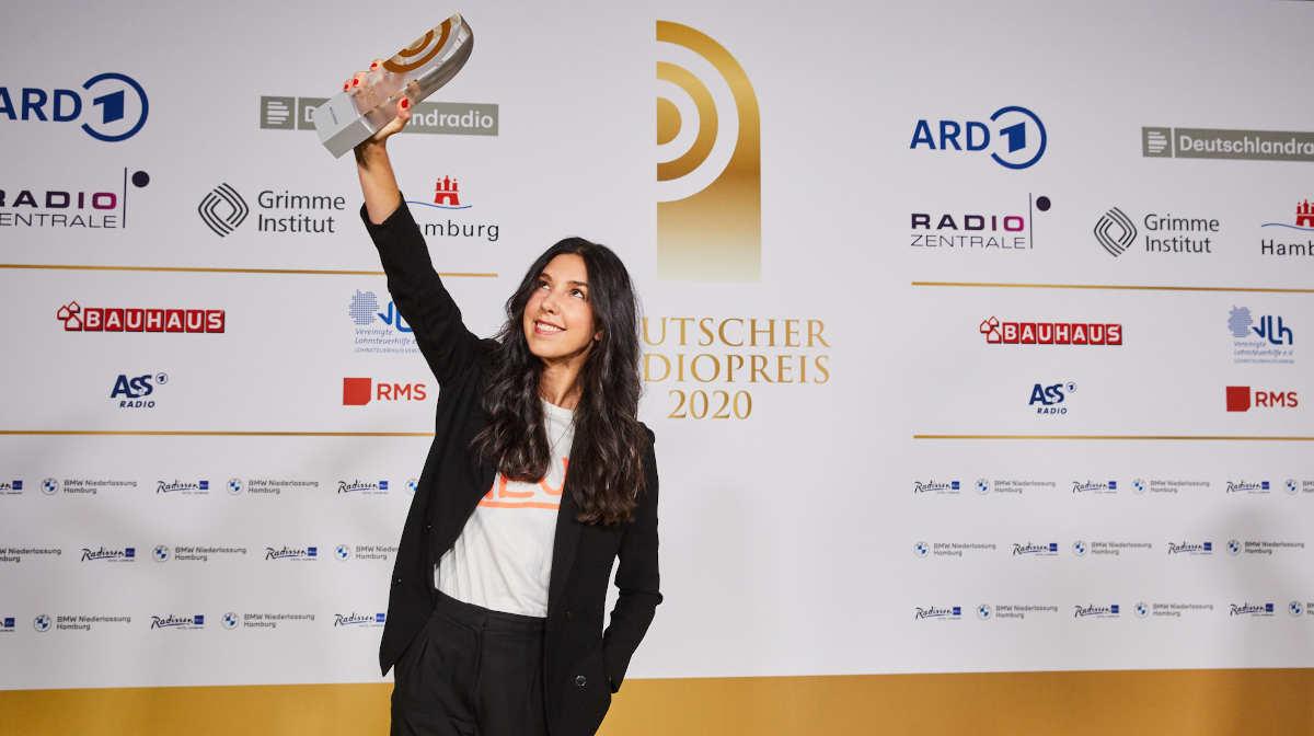 Deutscher Radiopreis 2020, das Bild zeigt Moderatorin Sandra Gern, wie sie stolz den Preis vor der Sponsorenwand zeigt