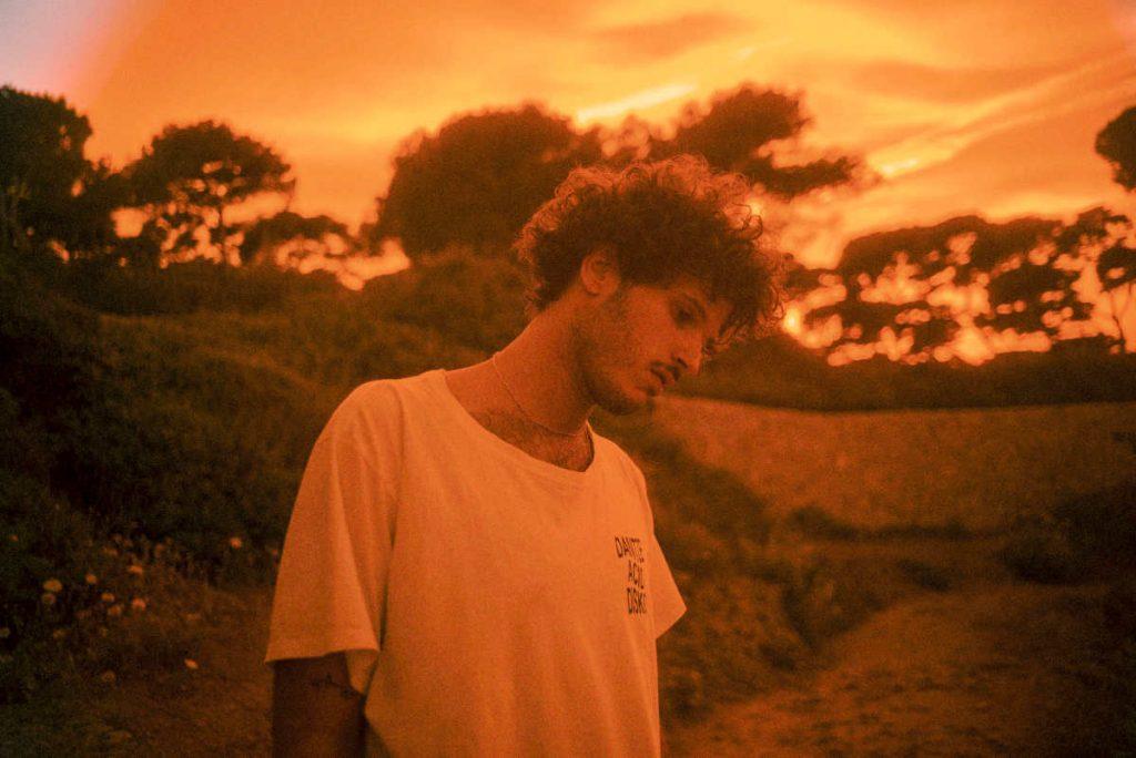 Ácido Flamenco Rave Club heißt die neue Radioshow von Kid Simius. Das Bild zeigt den Musiker mit einem weißen T-Shirt, im Hintergrund sind mediterrane Bäume vor einem Sonnenuntergang zu sehen.