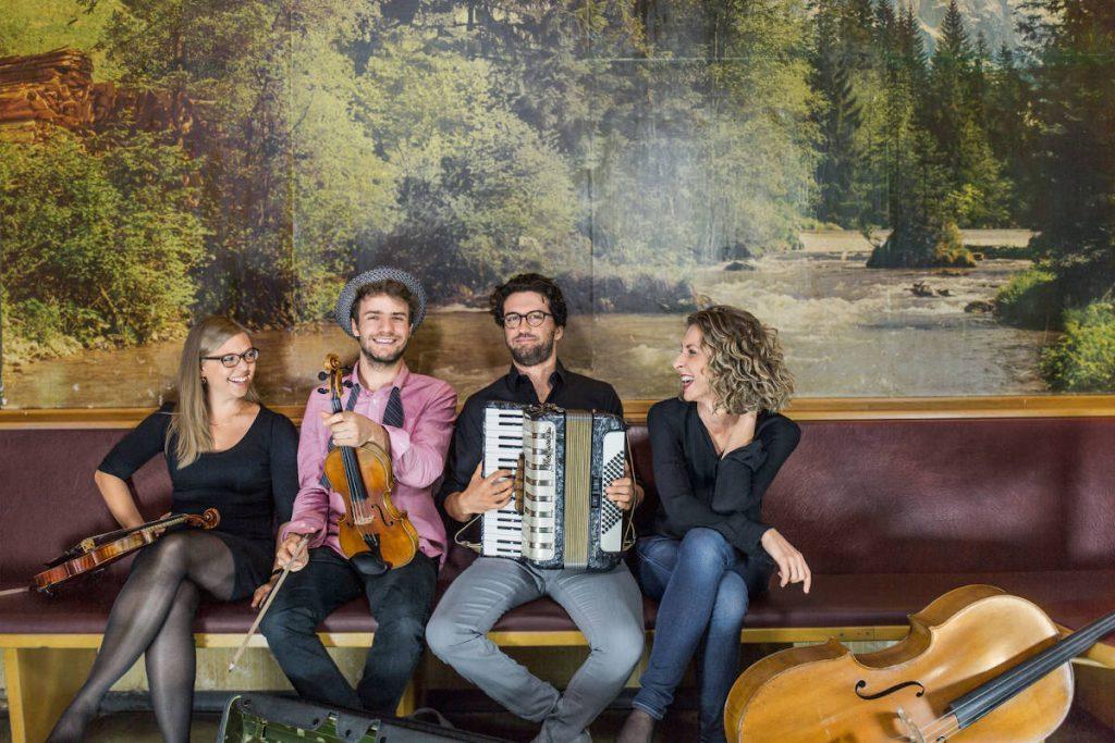 Nouwell Cousines auf dem Brunnenhof Open Air 2020, auf dem Pressefotos sitzen die vier Musiker*Innen auf einer Bank vor einem großem Wandgemälde