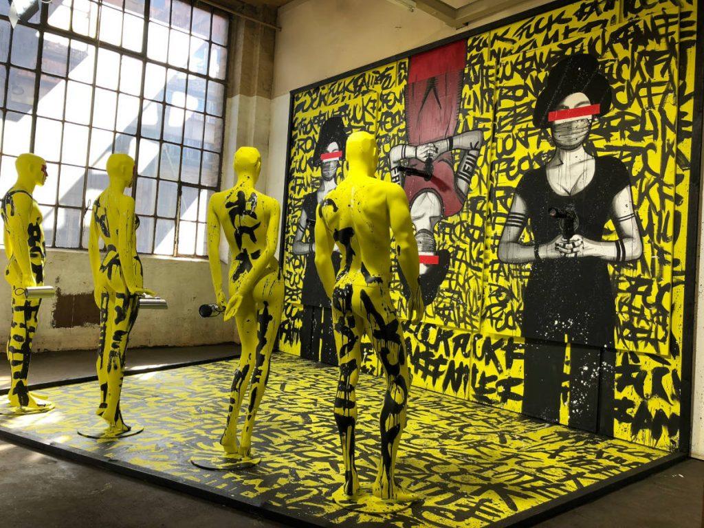 """Das Bild zeigt das Werk """"Monumenta"""" von """"Ron Miller"""", die auf der diesjährigen ARTMUC ausstellen. Das gesamte Werk ist in gelb und schwarz gehalten. Vier Schaufensterpuppen stehen vor einer Wand. Auf dieser Wand sind drei Geishas abgebildet, die Pistolen auf die Schaufensterpuppen richten."""