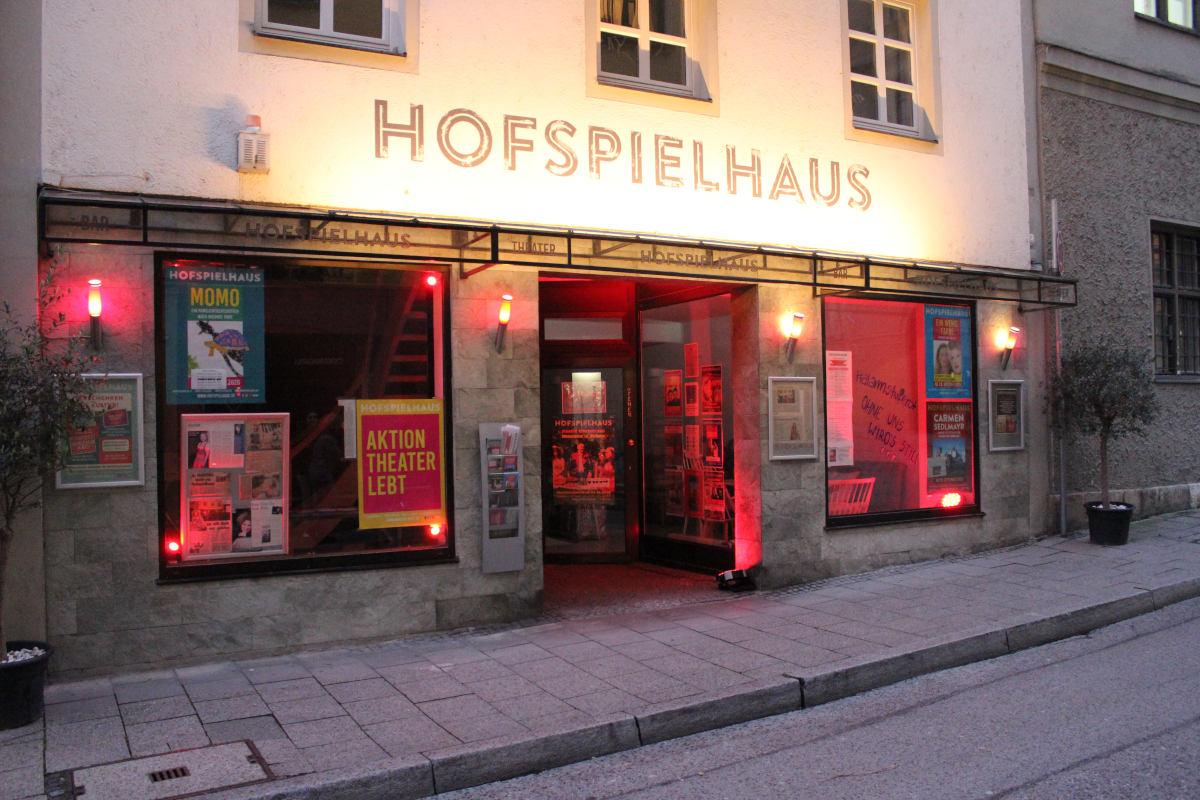 Klage gegen Theaterschließung - das Hofspielhaus von Außen, rot beleuchtet