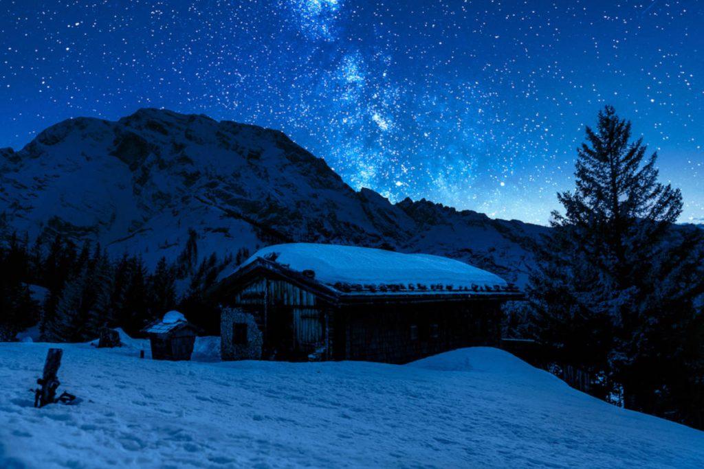 Das Bild zeigt eine kleine Hütte auf einem verschneiten Berg mit Sternenhimmel im Hintergrund.