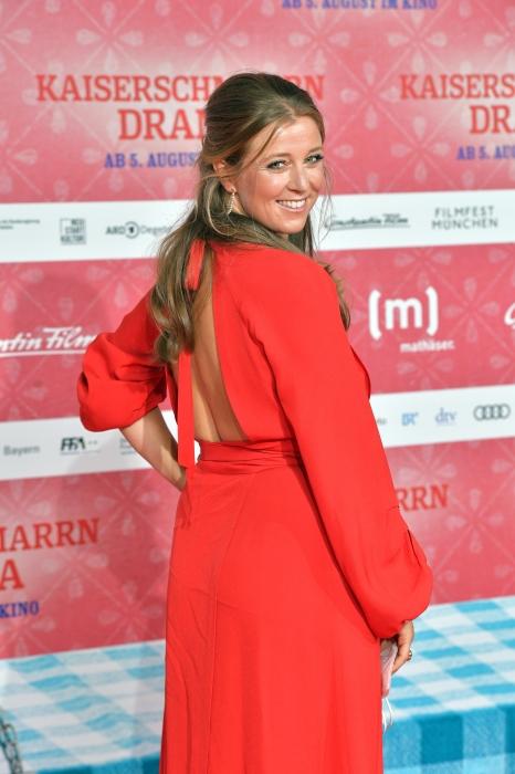 Nina Eichinger präsentiert ein rotes Kleid auf der Premiere zu Kaiserscharrndrama 2021