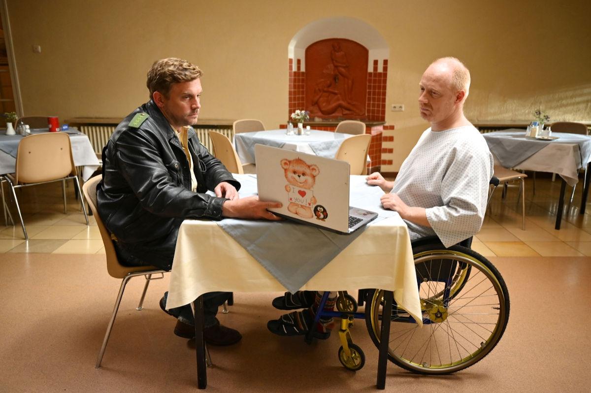 Eberhofer Birkenberger Krimis begeistern die Kinozuschauer*innen: Birkenberger in Polizeiuniform besucht seinen Ermittlerkollegen Birkenberger im Krankenhaus und zeigt ihm am Essenstisch neuste Erkenntnisse in einem Laptop.