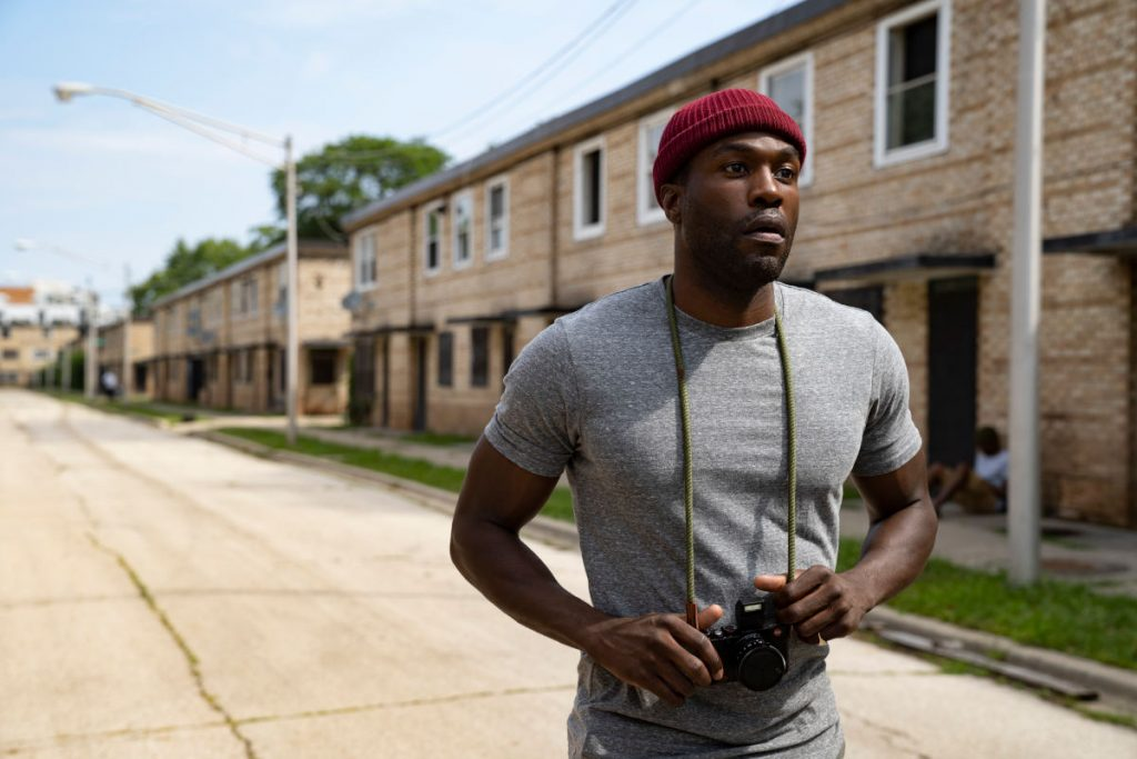 Horrorklassiker Candyman neu: Auf dem Szenenbild steht Hauptdarsteller Jordan Peele auf der Straße in einem ruhigen Wohngebiet und schaut die Straße hinunter. Er trägt eine rote Mütze und hat einen alten Fotoapparat um den Hals hängen.